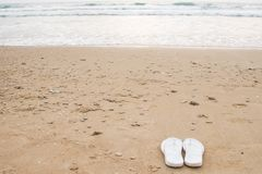 White slippers on golden sand. White female slippers lie on the sand by the sea royalty free stock images