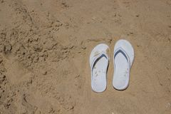 White slippers on golden sand. White female slippers lie on the sand by the sea stock photos