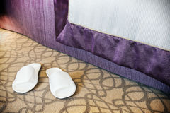 White slippers near the bed in the hotel Royalty Free Stock Photos