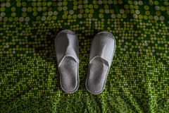 White slippers. A top view shot of a pair of white slippers on a colourful fabric Royalty Free Stock Images