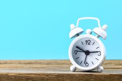 White small alarm clock on a wooden shelf on a blue pastel background. Minimalism.  Stock Photos