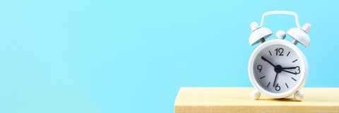 White small alarm clock on a wooden shelf on a blue pastel background. Minimalism.  Stock Photo