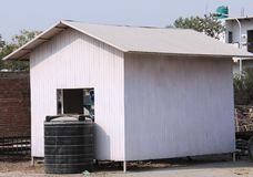 A white small cabin with black water tank Royalty Free Stock Image