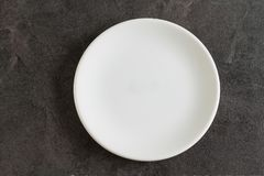 White small empty plate on dark background. White small empty plate on dark stone background Stock Images