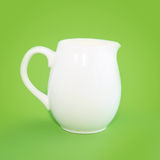 White small jug on a green background Stock Images