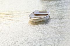 White small old fishing boat on river with sun on the side royalty free stock image