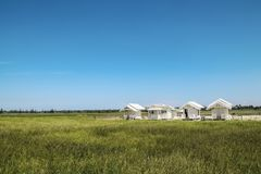 White small wooden house in the field. And blue sky background Stock Image