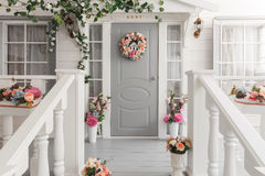 White small wooden house with gray door. spring flower decoration.  Royalty Free Stock Images