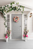 White small wooden house with gray door. spring flower decoration.  Stock Photography