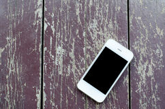 White smart phone with black screen on old dirty wooden backgrou. Nd - vintage tone royalty free stock photo