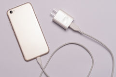 of white smart phone, charger with cable royalty free stock image