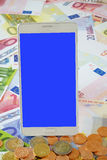 White Smart phone on Euro banknotes. White smart phone with blue blank touchscreen on a background of Euro banknotes and coins Stock Images