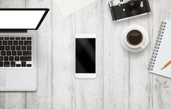 White smart phone with isolated screen for mockup on office desk. Royalty Free Stock Photo