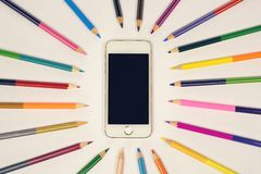 White smart phone on a light background, colored pencils around. Top view on office desk. mock up sample.  stock photos