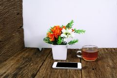 The white smart phone on wood table with a cup of tea Stock Photography