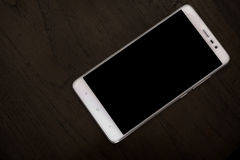 White smart phone on wooden table Royalty Free Stock Image