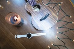 White Smart Watch with Decor. White Smart Watch w/ Ukulele, Candle, Headphones, Candle, Lights on Table top stock photos