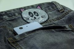 White smartphone in the back pocket gray jeans with appliqué of strasses. White smartphone in the back pocket gray jeans with appliqué rhinestones Stock Photo