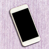 White smartphone with black screen on pink table background. Royalty Free Stock Photos