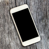 White smartphone with black screen on rustic timber background. Royalty Free Stock Images
