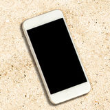 White smartphone with black screen on white sand background. Stock Images