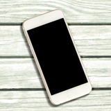 White smartphone with black screen on white timber background. Royalty Free Stock Image