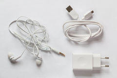 White smartphone charger, USB Cable and white earphones on a white background. Stock Images