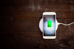 White smartphone charging on a charging pad. Stock Photos