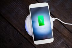 White smartphone charging on a charging pad. Royalty Free Stock Photos