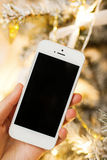 White smartphone with the christmas tree in background Royalty Free Stock Photos