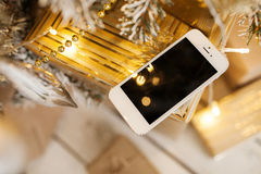 White smartphone with the christmas tree in background Royalty Free Stock Image