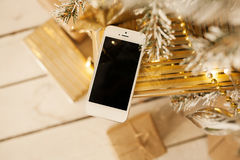 White smartphone with the christmas tree in background Royalty Free Stock Photography