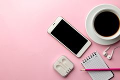 White smartphone and a cup of coffee and office supplies on a bright pink background. view from above royalty free stock photo