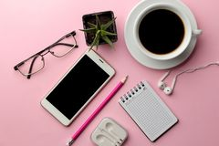 White smartphone and a cup of coffee and office supplies on a bright pink background. view from above royalty free stock photography