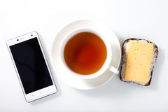 White smartphone,  a cup of tea and sandwich on white glass tabl Royalty Free Stock Images