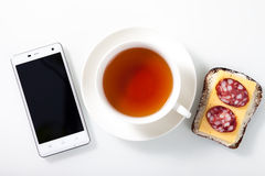 White smartphone,  a cup of tea and sandwich on white glass tabl Stock Photography
