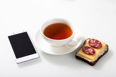 White smartphone,  a cup of tea and sandwich on white glass tabl Royalty Free Stock Photography