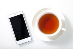 White smartphone and a cup of tea on white glass table Stock Image