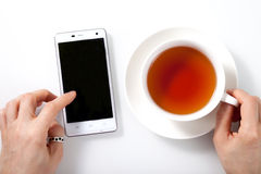 White smartphone and a cup of tea on white glass table and woman Royalty Free Stock Photography