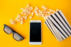 A white smartphone, 3d glasses, black and white striped paper box and scattered popcorn lie on a yellow background. royalty free stock photos