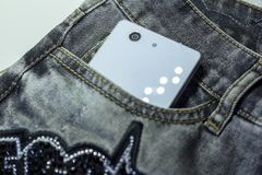 White smartphone in the front pocket gray jeans with appliqué of strasses. White smartphone in the front pocket gray jeans with application from rhinestones Royalty Free Stock Photos