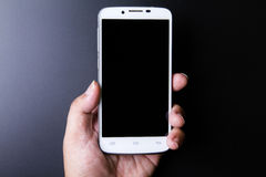 White smartphone in hand concept on dark background Royalty Free Stock Photo