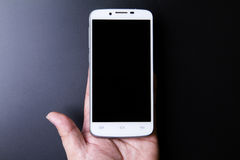 White smartphone in hand concept on dark background Stock Images