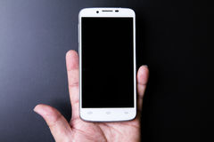 White smartphone in hand concept on dark background Stock Photo