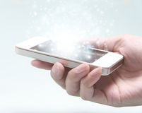 White smartphone with hand isolated on light background. Royalty Free Stock Image