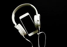 White smartphone and headphones banner template with text place. White headphones and telephone on black. White smartphone and headphones banner template with Stock Images