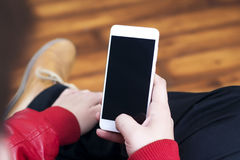 White smartphone holding in hand in standing position.  Royalty Free Stock Image