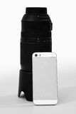 White Smartphone Leaning on Large DSLR Lens Royalty Free Stock Photography