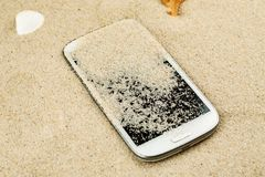 White smartphone lost in sand on the beach.  stock image
