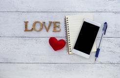 White smartphone and wooden love Royalty Free Stock Photography